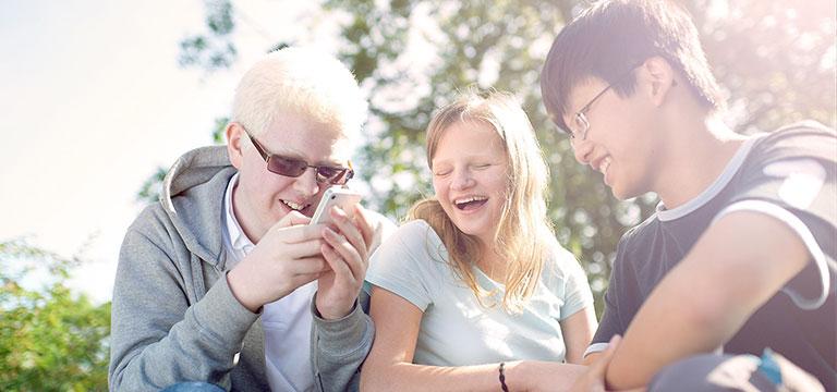Drei blista-Schüler sitzen in der Sonne und schauen lachend auf ein Smartphone