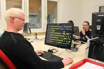Ein IT-Auszubildender mit Sehbehinderung an seinem entsprechend ausgestatteten PC