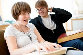 Zwei Schüler lesen vergnügt in einem Punktschriftbuch