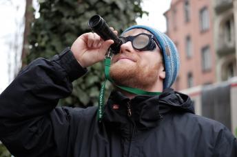 Ein Mann Schaut durch eine Lupe, um sich im Stadtverkehr zu orientieren
