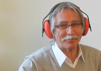 Ein Mann liest vergnügt per Kopfhörer