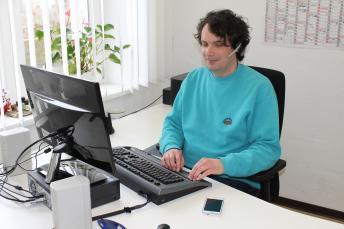Ein Mann arbeitet am blindenspezifisch ausgestatteten PC-Arbeitsplatz