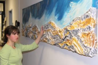 """Eine Schülerin steht vor dem taktilen Wandgemälde """"Fels in der Brandung"""""""