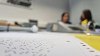 Das Foto zeigt ein liegendes Blatt Papier mit Punktschrift im Vordergrund, der Hintergrund verschwimmt