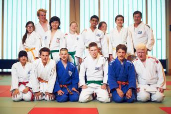 Das Foto zeigt eine der blista-Judoka-Gruppen: 13 Mädchen und Jungen in blauen und weißen Anzügen mit ihrem Trainer