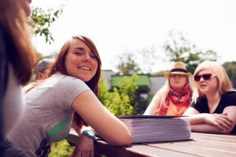 blista-Schülerinnen sitzen gemeinsam an einem Tisch im Sonnenlicht
