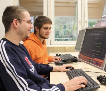 2 IT-Auszubildende arbeiten mit Textvergrößerung und Screenreader