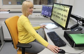 Eine junge Frau am sehbehindertengerecht eingerichteten Büro-Arbeitsplatz