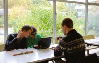 Kai Kortus sitzt mit einem Notebook am Tisch, neben ihm zwei Kommilitonen
