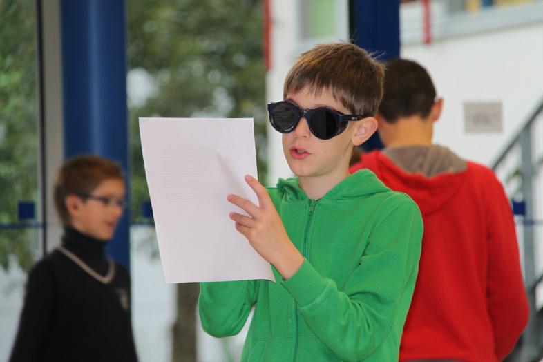 Lesen mit Simulationsbrille - ein Montessori-Schüler macht sich mit Blindheit und Sehbehinderung vertraut