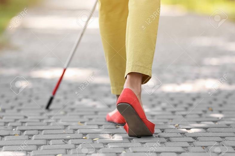 Foto zeigt die Füße und Langstockspitze einer blinden Frau beim Gehen über Pflastersteine