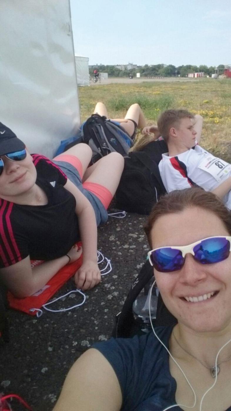 Die Gruppe chillt im Schatten hinter einem Umkleidezelt