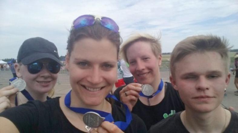 Die Läufer und Läuferinnen präsentieren ihre Medaillen