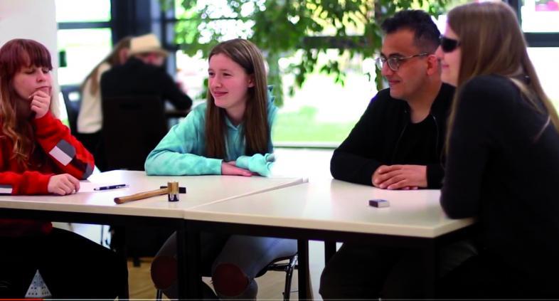 Valery, Nele, Furkan und Aileen sitzen draußen an einem Tisch