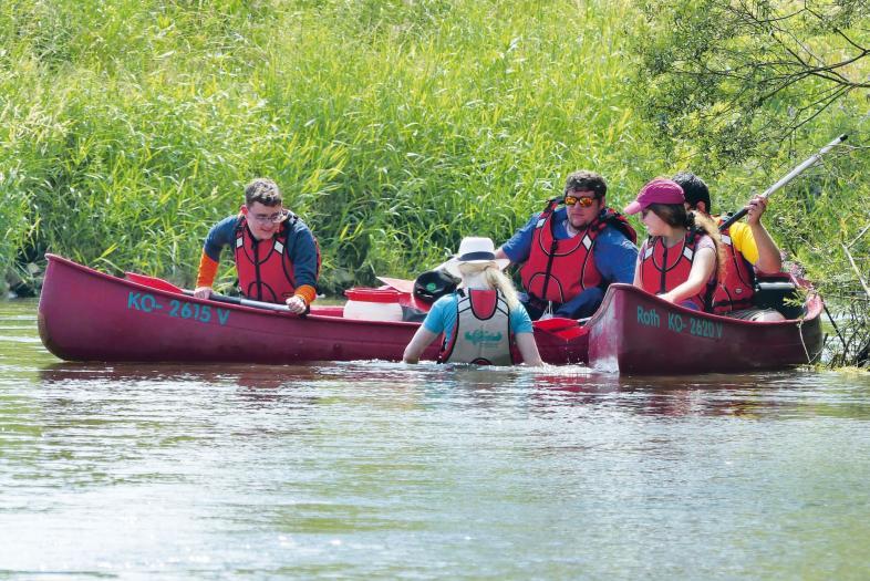 Eine Schülerin in T-Shirt, Schwimmweste und Hut steht im Wasser zwischen zwei voll besetzten Kanus.