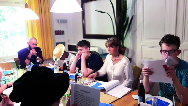 Fünf Personen sitzen am Tisch und sind ins Nachdenken versunken. Einer mit Strohhut studiert seine Unterlagen, einer stützt den Kopf auf beide Hände.