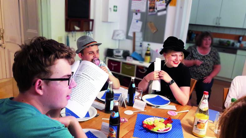 Am schick gedeckten Esstisch sitzen eine blonde Dame mit schwarzem Hut, ein Schnauzbartträger mit Seppl-Hut und ein junger WG-Bewohner mit aufgeschlagenem Script. Alle blicken erwartungsvoll nach rechts.