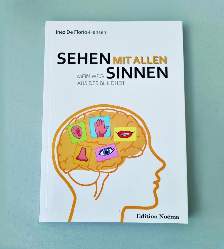 Buchcover von Inez De Florio-Hansen, Sehen mit allen Sinnen. Abgebildet ist ein Kopfumriss im Profil mit eingezeichneten Hirnarealen für die verschiedenen Sinnesmodalitäten.