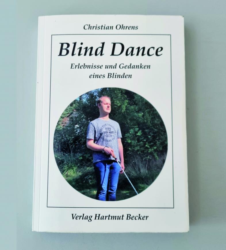 Buchcover von Christian Ohrens, Blind Dance. Das Cover ist weiß mit schwarzer Beschriftung und einem runden Fotoausschnitt eines jungen Mannes in Jeans und T-Shirt mit Langstock.