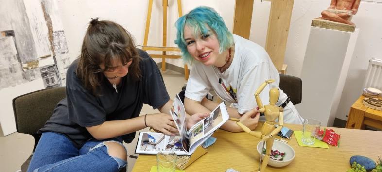 Sina und Katharina blättern im Foto-Erinnerungsbuch.