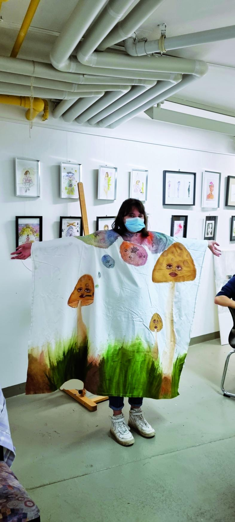 Sina präsentiert einen im Atelier gestalteten Umhang. Er war ursprünglich weiß und wurde mit mehreren Pilzen mit Gesichtern und weiteren bunten  Bildern bemalt.