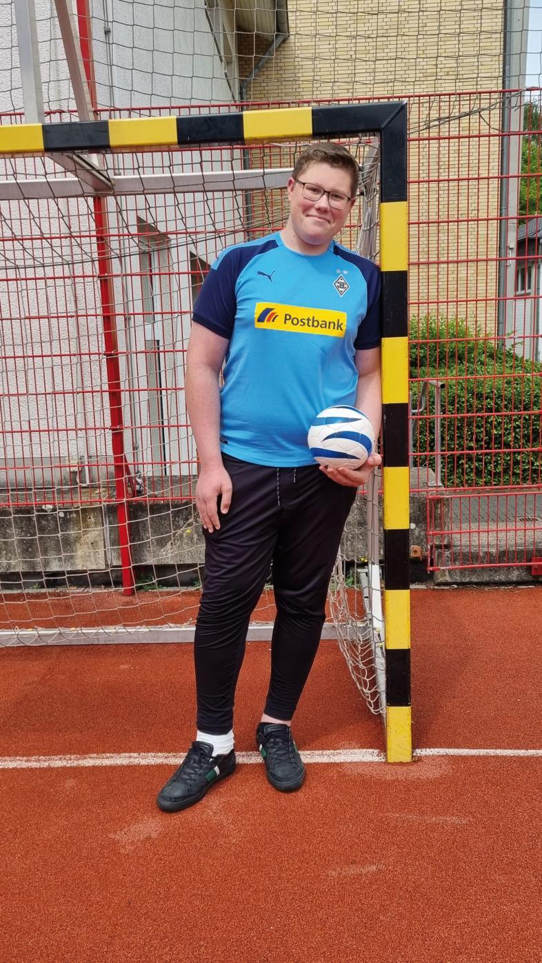 Ein Foto eines jungen Fußballers mit Brille, Sportkleidung und einem Blindenfußball in der Hand.