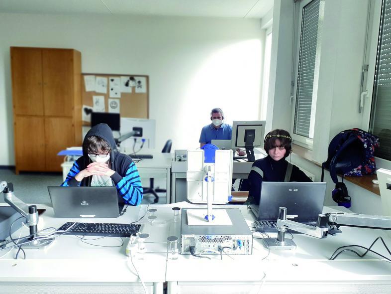 Die Mitglieder des Englisch-Teams Luca und Amelie mit Lehrer Jens Flach konzentriert vor den Laptops.