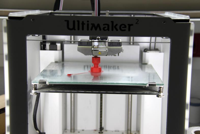 3-D-Drucker in Aktion: Man kann bereits eine kleine rote Figur erkennen