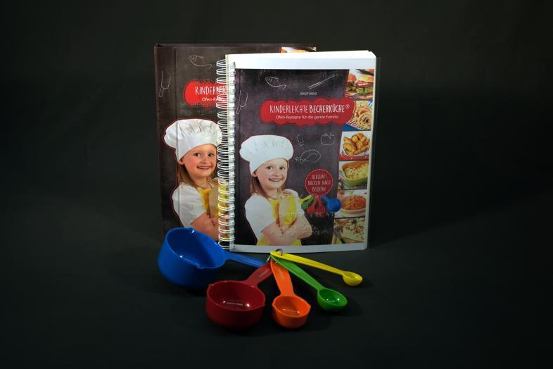 Buchcover des Kochbuchs mit ausgebreiteten verschiedenfarbigen Messbechern