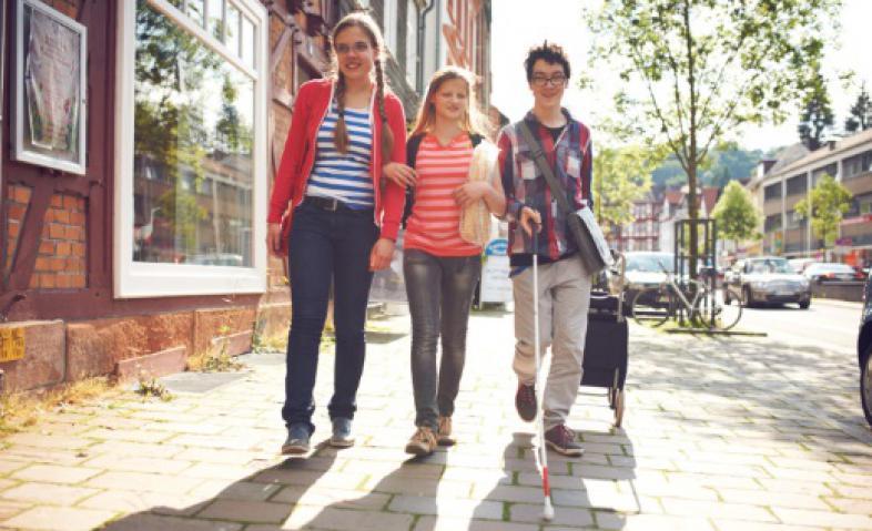 Zwei Mädchen und ein Junge mit Shopper auf dem Rückweg vom Einkaufen.