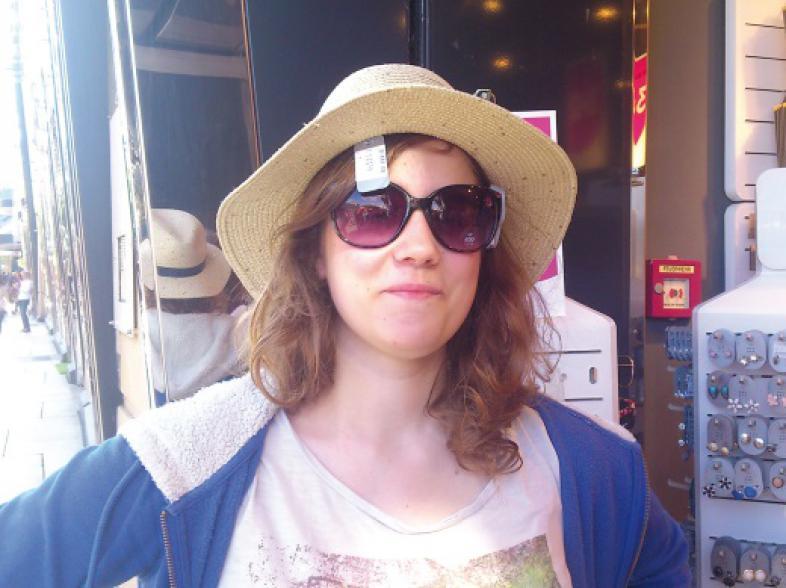 Junge Frau mit Sonnenbrille probiert einen Strohhut auf