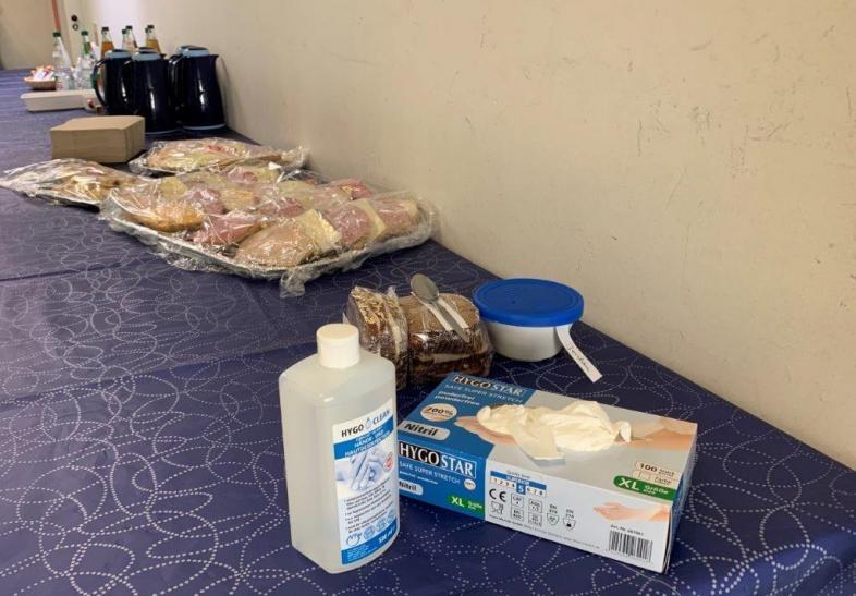 Das Foto zeigt, die sorgfältig eingehaltenen Hygienevorschriften: Die belegten Brote sind einzeln verpackt, Handschuhe und Hygieneflüssigkeit liegen bereit