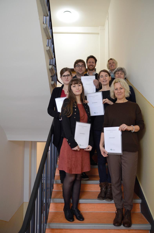 Die glücklichen Absolventen stehen auf einer Treppe