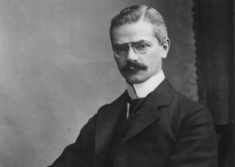 Alfred Bielschowsky sitzt auf einem Stuhl, am unteren Rand des fotos ist die Unterschrift von A. Bielschowsky zu sehen