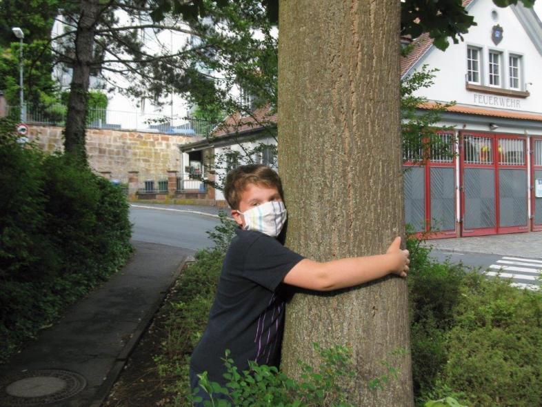 Ein Junge trägt die Mund-Nase-Schutzmaske und umarmt einen Baum
