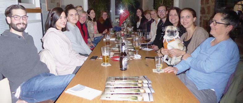 Beim AK_Stammtisch sitzen junge Leute an einem langen Tisch