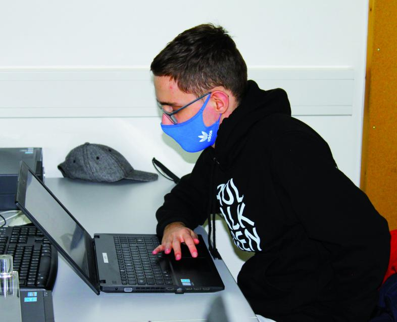 Jonas arbeitet mit Maske an seinem Laptop