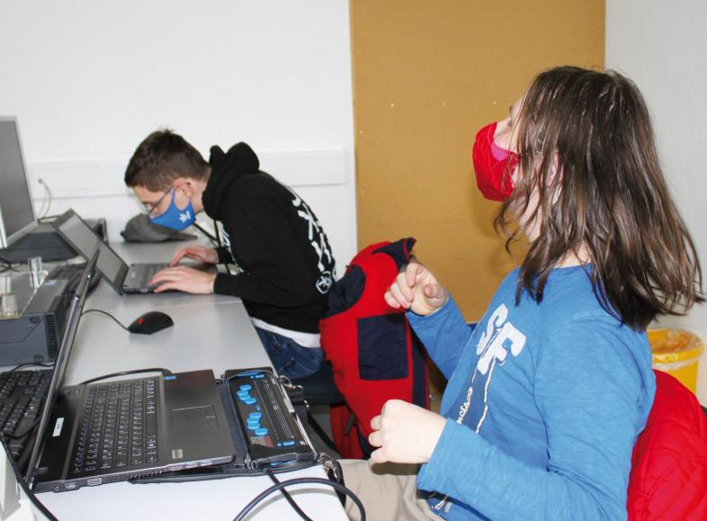 Jonas und Steve mit Abstand und Masken beim Präsenzunterricht