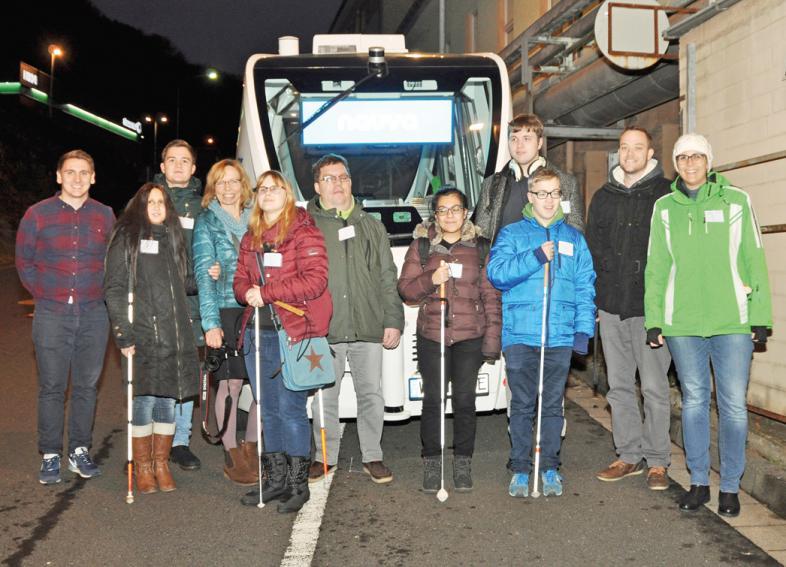 Nach der Fahrt stehen Schüler und Mitarbeiter der Deutschen Blindenstudienanstalt, Marburg, mit dem Team des R+V Innovation Labs vor dem selbstfahrenden Kleinbus.