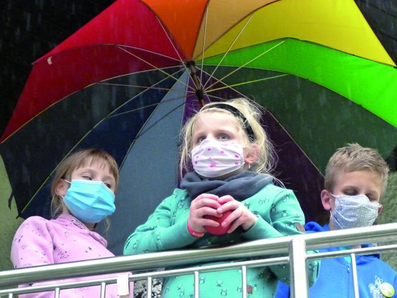 Die Autorin Alexandra, Isabel und Julian, alle mit Mundschutz, unter einem bunten Regenschirm