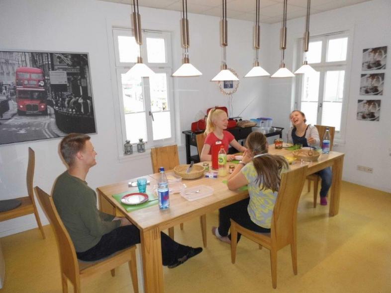 Mahlzeit in der WG: 3 Schüler*innen und ein Betreuer sitzen am langen Tisch mit viel Abstand