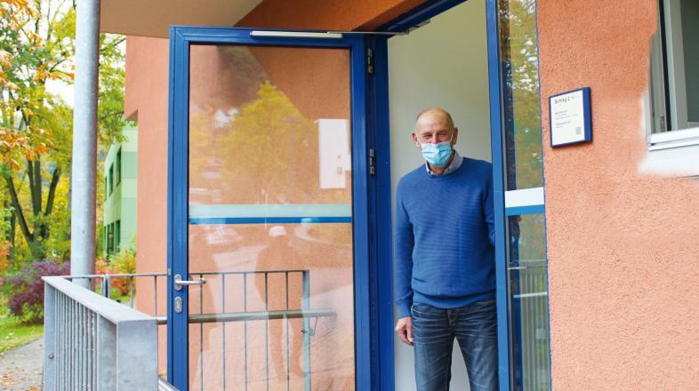 Dr. Bernd Scheid schaut aus dem Eingang zum Betriebsarztzimmer unterhalb der Aula