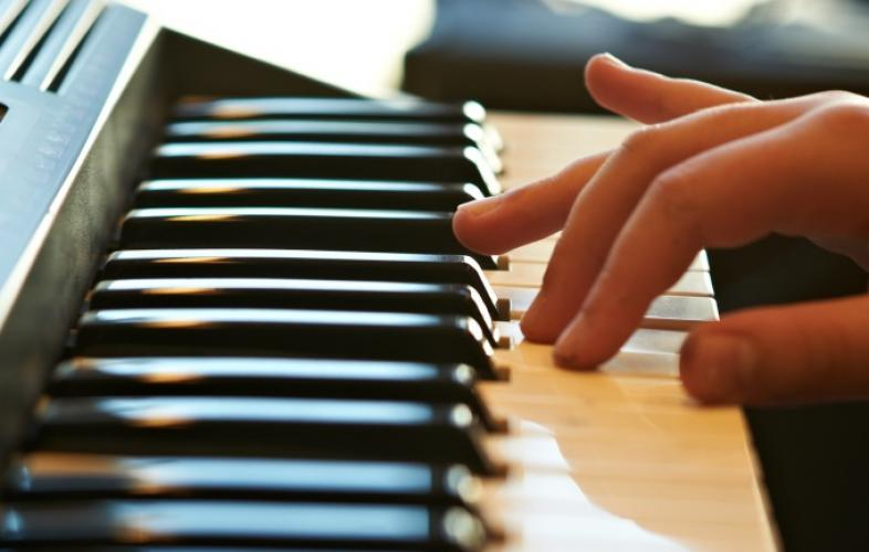 Eine Hand spielt auf der Tastatur eines Keyboards