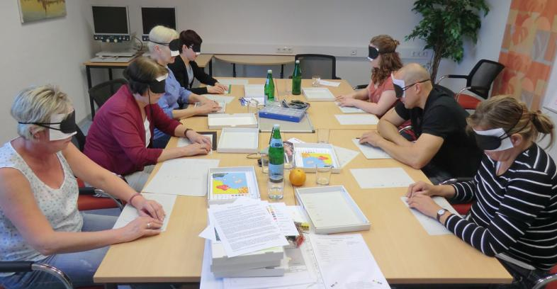 Eine Gruppe von 7 Personen sitzt in einer Tischrunde und ertastet Materialien unter Augenbinden.