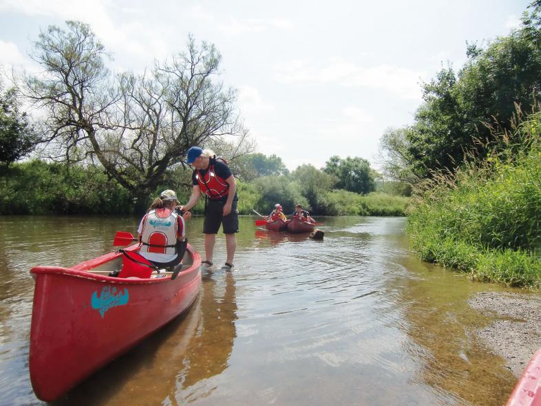 Foto von 3 besetzten Kanus im seichten Wasser der Lahn. Beim Kanu im Vordergrund ist Gerald, einer der Betreuer, noch nicht eingestiegen.