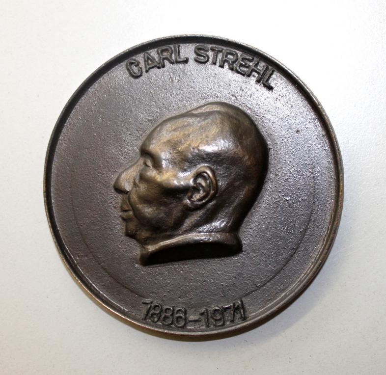 Carl-Strehl-Plakette zeigt das Profil Carl Strehls und ist mit Geburts- und Sterbetag versehen. Sie zeigt zudem die Abkürzungen beider Einrichtungen, des VBGD (heute DVBS) und der Deutschen Blindenstudienanstalt.