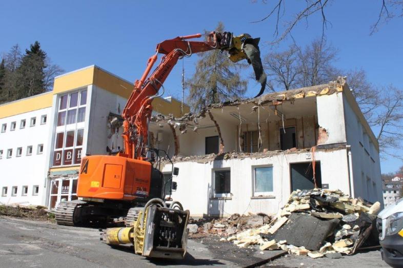Der große Bagger vor dem DBH-Gebäude beginnt mit dem Abriss der Aussenfassade.