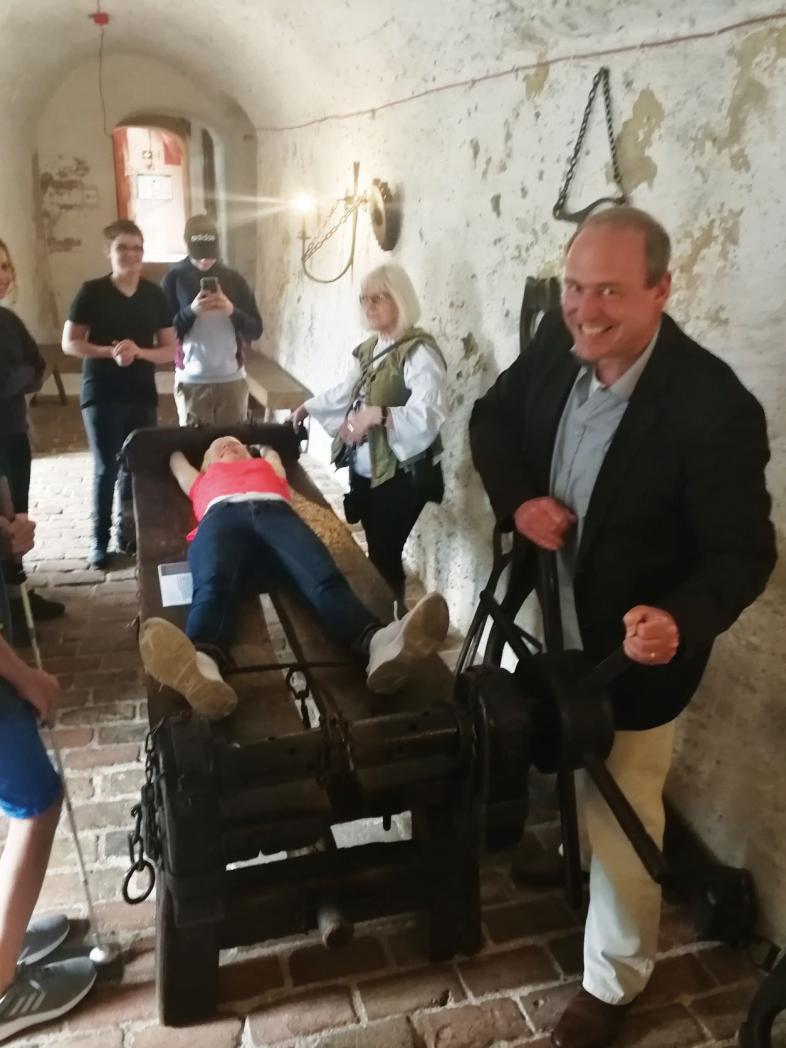 Leonie wird auf die Folter gespannt, während Herr Roos diabolisch grinst.
