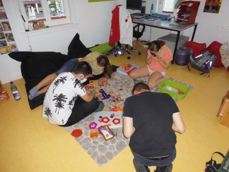 Vier Schüler*innen spielen gemeinsam auf dem großen Spielteppich, alle tragen Schutzmasken