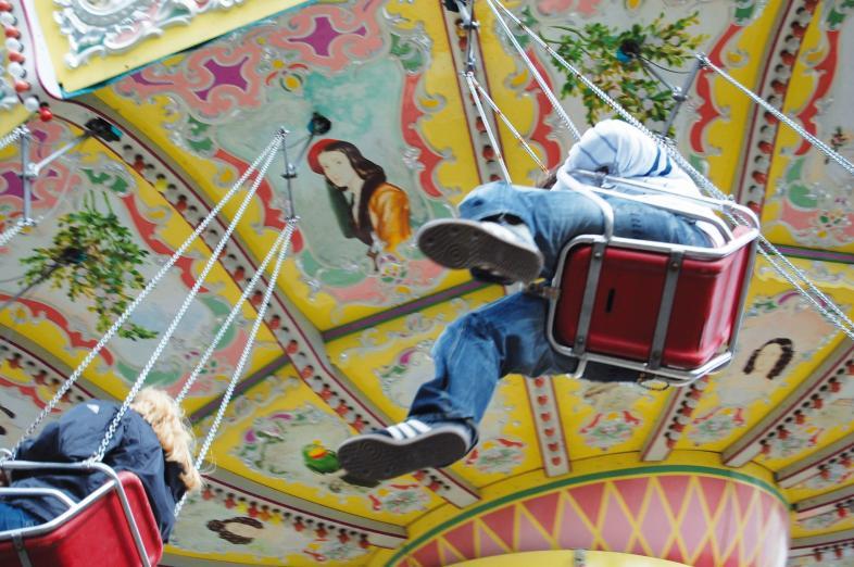 Foto vom fahrenden Kettenkarussel mit Passagieren von unten. Man sieht Schuhsohlen, Beine, eine Sitzfläche und die Bemalung des Karusseldaches.